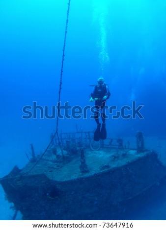 Diver in front of bow of Halliburton shipwreck, Utila - stock photo