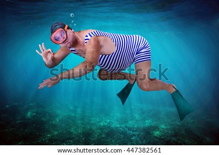 Diver in retro swimsuit swims underwater and shows gesture O.K. Swimmer examines the seabed. Vacation at sea. Man snorkeling in the tropical sea. Vintage style man with flippers diving under water. - stock photo