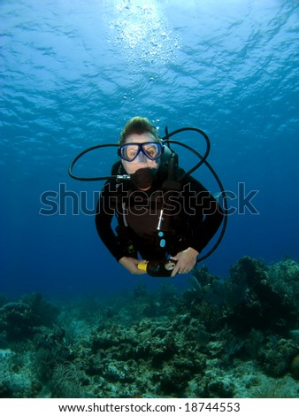 Diver looking into the Camera on a Cayman Island Reef - stock photo