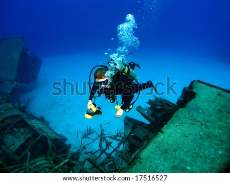 Diver photographing a Sunken Shipwreck in Cayman Brac - stock photo
