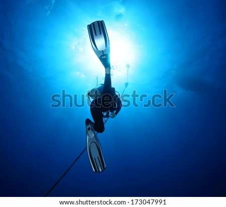 Diver silhouette under water with beautiful sun ray. - stock photo