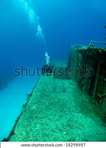 Diver swimming along side a Sunken Shipwreck in Cayman Brac - stock photo