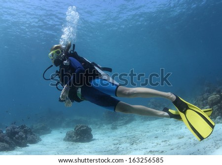 Diver swimming over sandy area in a tropical clear sea - stock photo