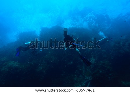 Diver swimming to sea surface with wave above