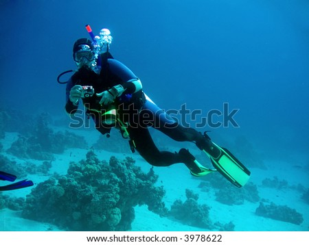 diver with camera in deep. underwater photographer - stock photo