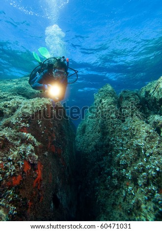 Diver with underwater light by reef - stock photo