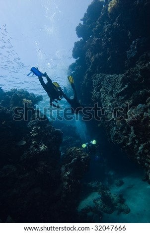 Divers entering an underwater cave - stock photo