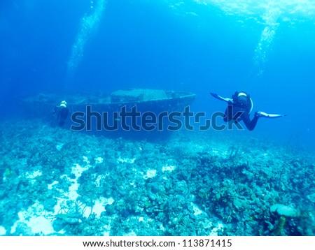 divers explore a wrack - stock photo