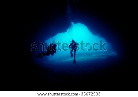 divers in a cave - stock photo