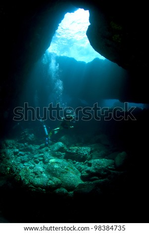 Divers in a Lava tube in Kona Hawaii - stock photo