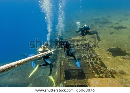 Divers under wreck - stock photo