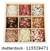 Diverse beans in wooden box sections isolated on white - stock photo