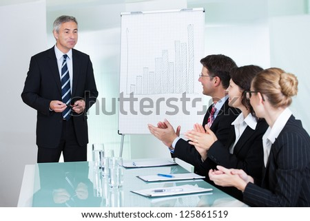 Diverse business colleagues seated around a table clapping after a staff presentation by a manager or senior executive - stock photo