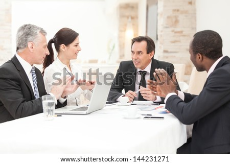 Diverse business group applauding during corporate meeting. Horizontal shot. - stock photo