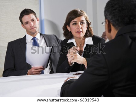 Diverse business people conversing and negotiating, focus on businesswoman, 40s - stock photo