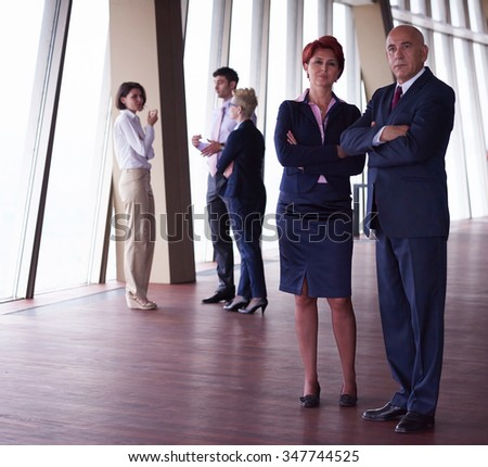 diverse business people group standing together as team  in modern bright office interior  with redhair senior woman in front as leader