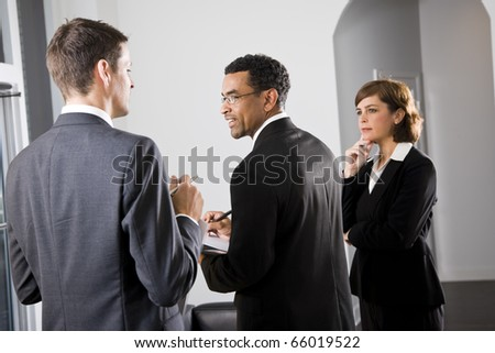 Diverse businesspeople conversing and taking notes, focus on African American man in middle - stock photo