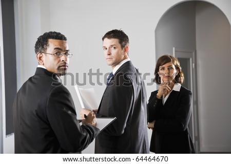 Diverse businesspeople meeting, looking over shoulder at viewer, focus on man in middle - stock photo