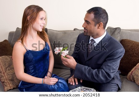 Diverse couple with man offering teenager flowers.