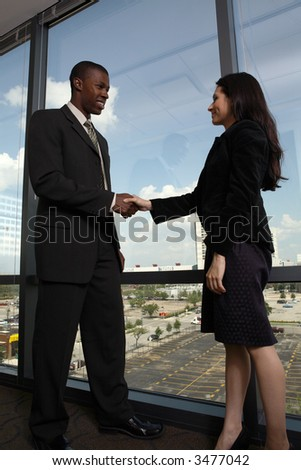 diverse coworkers shaking hands inside