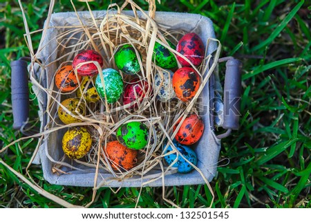 Diverse Easter eggs in a basket, placed on a grass - stock photo