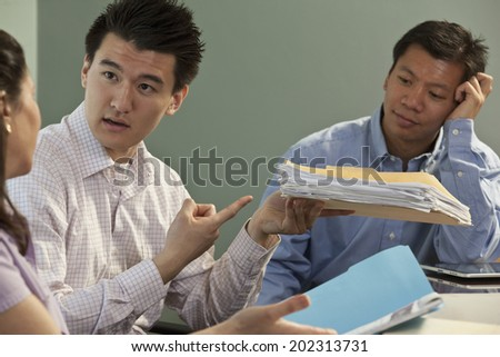Diverse ethnicity business colleagues discussing company plans during a conference room meeting. - stock photo