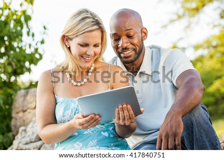 Diverse friends watching a video on a tablet device at the park - stock photo