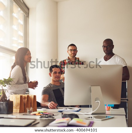 Diverse group of Black, Hispanic and Caucasian young adult entrepreneurs together at small business office with large bright window - stock photo