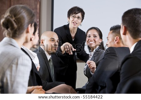 Diverse group of businesspeople conversing with woman standing at front