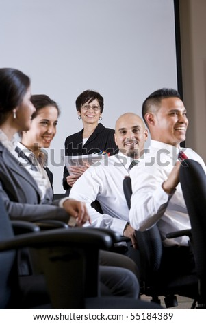 Diverse group of businesspeople watching presentation - stock photo