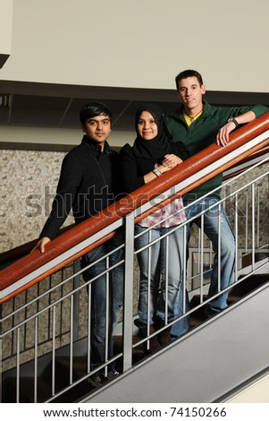 Diverse group of College students standing on the stairs inside a university building - stock photo