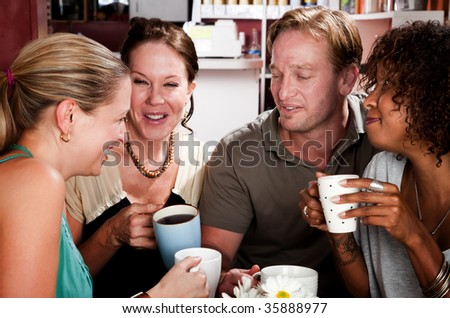 Diverse group of four friends in a coffee house - stock photo