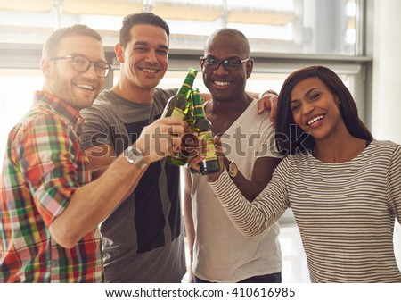 Diverse group of four young smiling friends in casual outfits tapping green glass beer bottles - stock photo