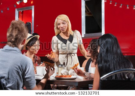 Diverse group of friends eating pizza slices from food truck - stock photo