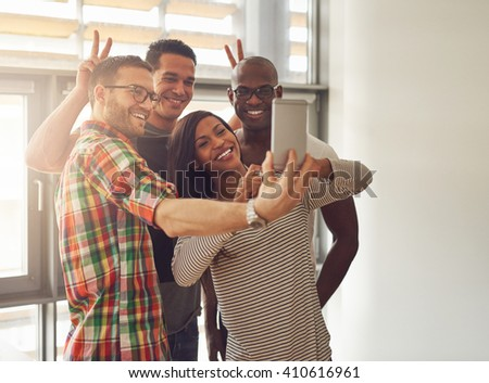 Diverse group of happy young workers taking pictures and making symbolic hand gestures for camera phone at small office in front of bright windows - stock photo