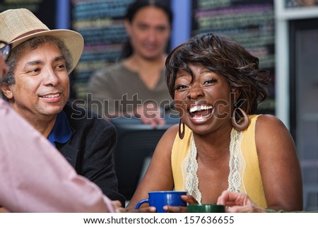 Diverse group of men and women laughing in restaurant - stock photo