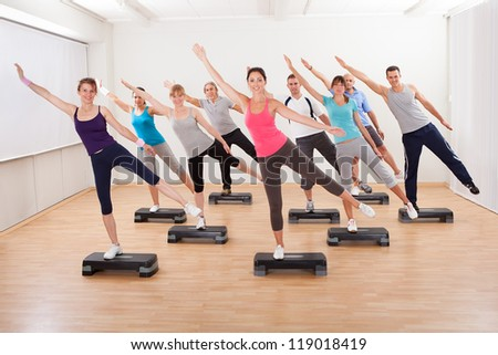 Diverse group of people in a class doing aerobics balancing on boards exerting control over their muscles and breathing