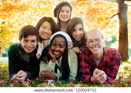 Diverse group of smiling friends in a pyramid in autumn - stock photo