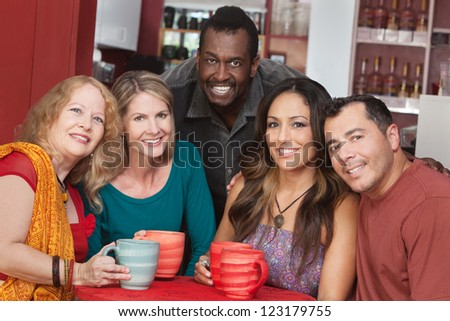 Diverse group of smiling mature adults in restaurant - stock photo