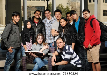 Diverse Group of Students in College Campus with buildings on the background - stock photo