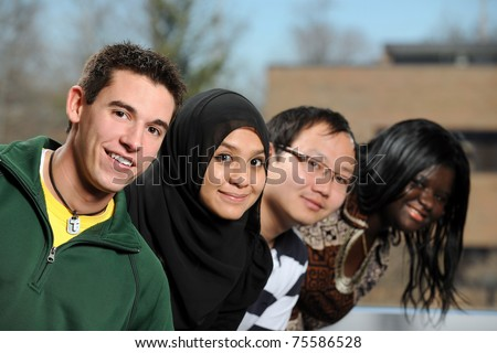 Diverse group of students smiling with selective focus on foreground person - stock photo
