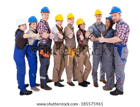 Diverse group of workmen and woman in their overalls and hardhats standing grouped in a semi circle giving a thumbs up gesture of approval and success  isolated on white - stock photo