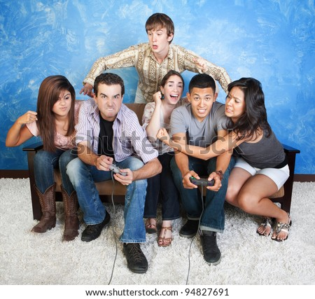 Diverse group of young people fight over video games - stock photo