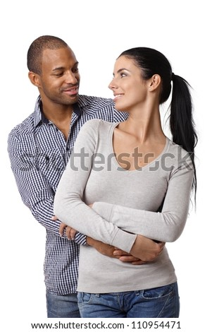 Diverse loving couple holding hands, embracing, smiling at each other. - stock photo