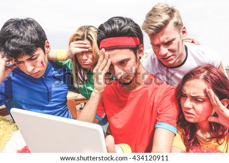 Diverse mix of friends sports fans watching football match on tablet outdoor - Disappointed supporter for a lost goal - Sadness feeling moment for sport concept - Main focus on center guy - stock photo