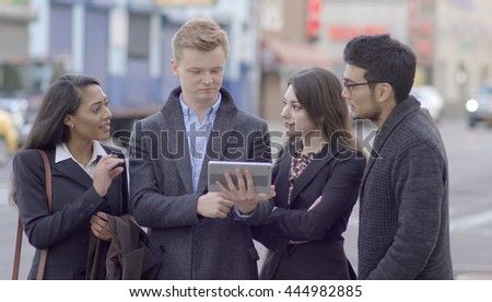 diverse multi ethic group of young people talking together standing on city street looking at tablet computer. happiness lifestyle background. teamwork passion spirit scene