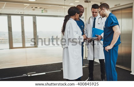 Diverse multiracial medical team consulting on a patient records standing in a foyer at a hospital grouped around a tablet computer - stock photo