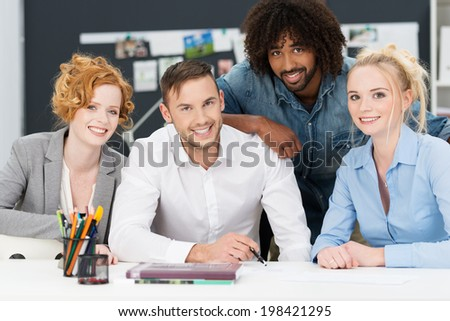 Diverse multiracial young business team in a creative office posing close together behind a desk in the office smiling at the camera - stock photo