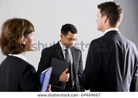 Diverse people in business suits, looking away from each other, focus on man wearing eyeglasses