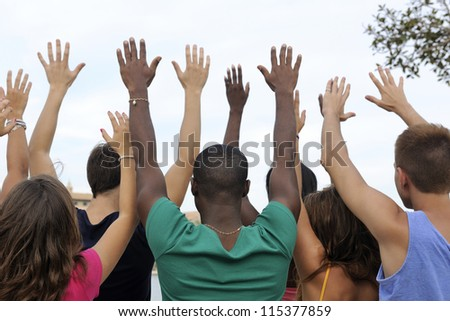Diverse volunteer group raising hands - stock photo